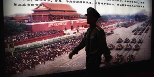 中国では毎年なんらかの警備・治安関連の展示会が開かれている。写真は2009年に開催された、警察装備および対テロ技術・装備の国際展示会の会場で、展示パネルの前を通りすぎる警備員を写したもの。© Feng Li/Getty AFP
