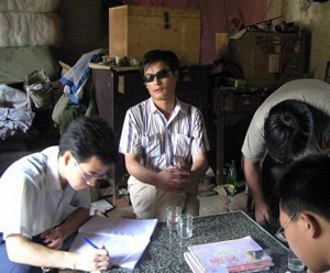 村人から人権侵害の聞き取りを行う陳光誠さん