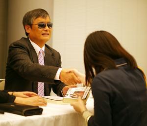 書籍を購入した来場者と握手をする陳光誠