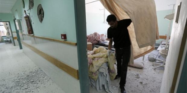 イスラエル国防軍の砲撃を受けたアル=アクサ病院の被害を調べるパレスチナ人の職員(ガザ地区中央、デイル・アル=バラ) © AFP/Getty Images