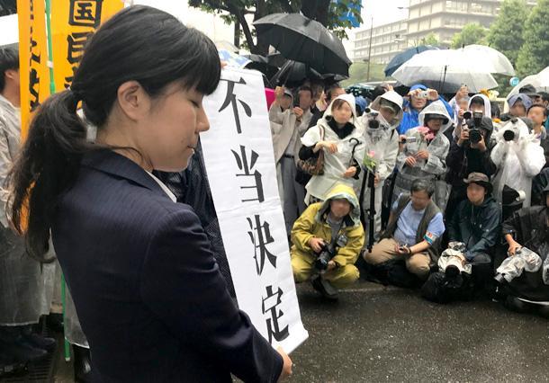 東京高裁前で「不当決定」の垂れ幕を掲げる弁護士