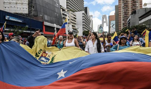 Protesters seen holding a huge Venezuela flag © Roman Camacho/SOPA/LightRocket/Getty