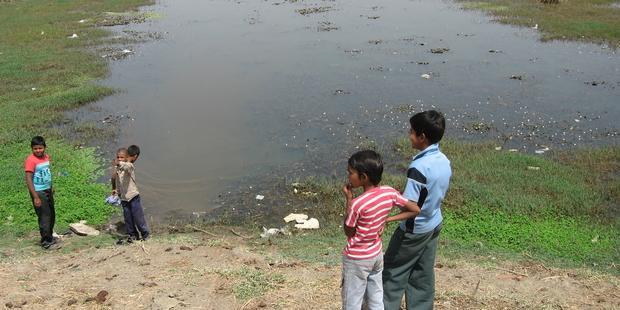 汚染された池のまわりで遊ぶ子どもたち (C)Amnesty International