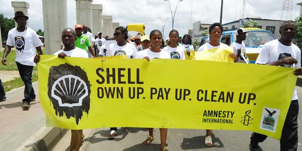 Activists in Port Harcourt, Nigeria protest to demand that Shell pay reparations and clean up its oil spills.