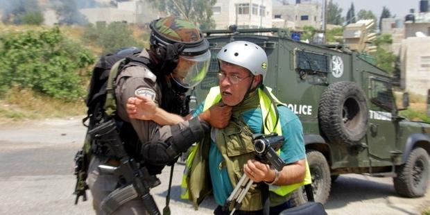 Bilal Tamimi being attacked by an Israeli soldier at a protest in Nabi Saleh in May 2013. (C) Tamimi Press
