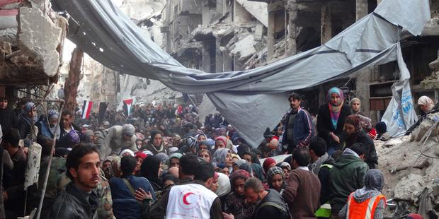 Desperate crowd awaits relief aid at Yarmouk Palestinian refugee camp in Damascus.(C) UNRWA Archives