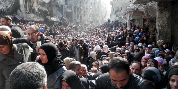 Residents wait to receive UNRWA food aid at the besieged al-Yarmouk camp on January 31, 2014.(C)unrwa.org