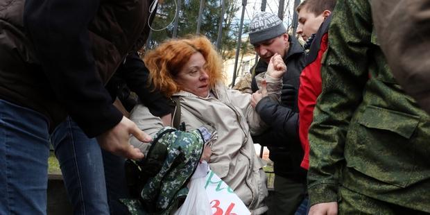 クリミア自警団と名乗る男性100人が、約40名の女性が行っていた平和的な抗議活動を無理やりやめさせた。(3月5日、クリミア自治共和国の首都シンフェロポリにて)(C) VOLODYMYR PETROV/AFP/Getty Images