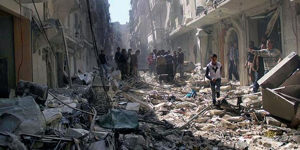 Syrians inspect the rubble of destroyed buildings following a Syrian government airstrike in Aleppo, March 2014.(C) AP Photo/Aleppo Media Center AMC