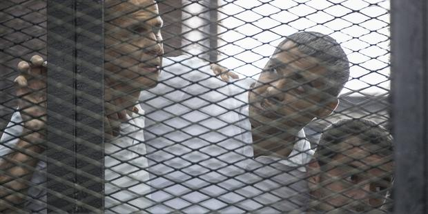 Al-Jazeera news channel's Australian journalist Peter Greste (L) and his colleagues, Egyptian-Canadian Mohamed Fadel Fahmy (C) and Egyptian Baher Mohamed , in the Egyptian court last year.(C)AFP/Getty Images