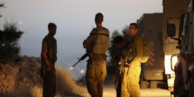 3人の遺体が発見された場所近くで検問に立つイスラエルの兵士 (C)HAZEM BADER/AFP/Getty Images