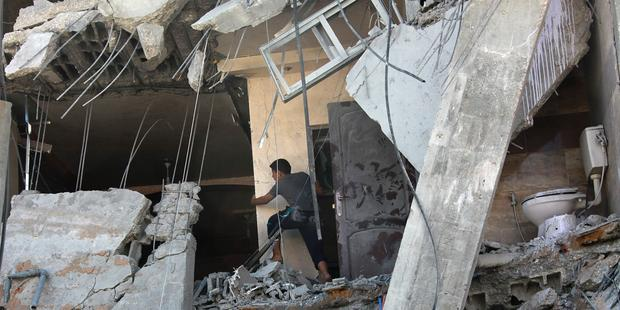 A member of the Palestinian Abu Lealla family examines the damage to his destroyed house following an Israeli airstrike north of Gaza City on, 11 July 2014.(C)EPA/MOHAMMED SABER