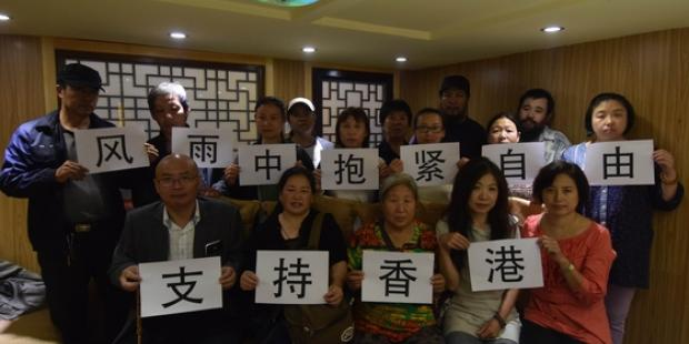 Beijing activists show support for democracy protests in Hong Kong on 29 September. The placards say 'Support Hong Kong' and 'embrace freedom in wind & rain'. 7 of this group remain in detention. (C) Private
