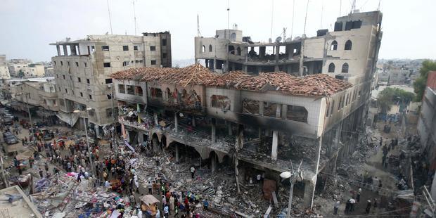瓦礫と化した商業施設の周りにたたずむパレスチナの人びと。目撃者によれば、イスラエルの空爆を受けたという。(C)REUTERS/Ibraheem Abu Mustafa