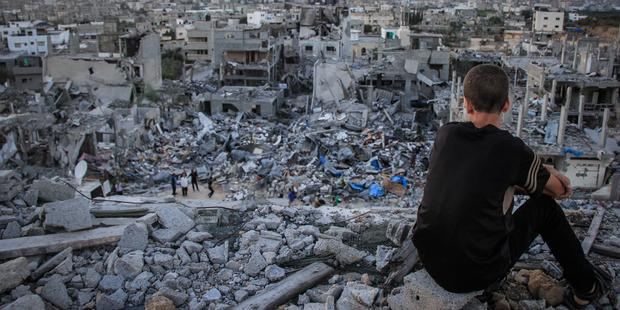 A Palestinian child sits above the ruins of his ruined home, and looks at thousands of homes destroyed because of the war on Gaza.(C)2014 Pacific Press