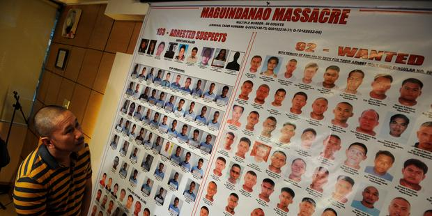 容疑者の写真を見つめるマギンダナオ州知事のエスマエル・マグダダトゥ氏。彼は、フィリピン最悪の政治的虐殺事件で親族を失った。(C)NOEL CELIS/AFP/Getty Images