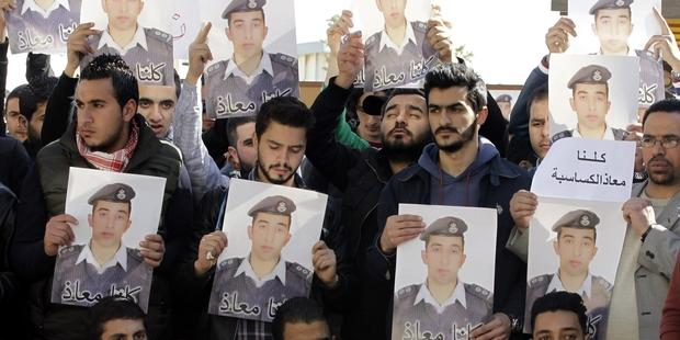 Activists carry posters with a portrait of the Jordanian pilot Maaz al-Kassasbeh. © KHALIL MAZRAAWI/AFP/Getty Images