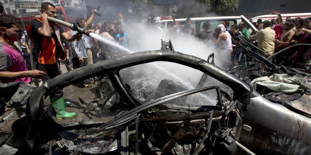 7月8日のイスラエルによるガザへの攻撃で標的にされた車両の消火にあたる消防士たち。(C) MOHAMMED ABED/AFP/Getty Images