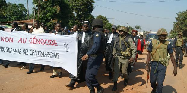 中央アフリカ共和国の首都バンギで警察の護衛を受けながら、暴力反対のデモをする人たち(C) PACOME PABANDJI/AFP/Getty Images