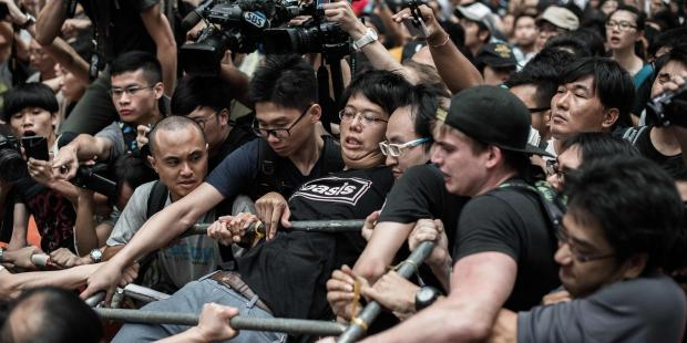 A pro-democracy protester (R) holds onto a barrier as he and others protect a barricade from rival protest groups in the Mongkok district of Hong Kong