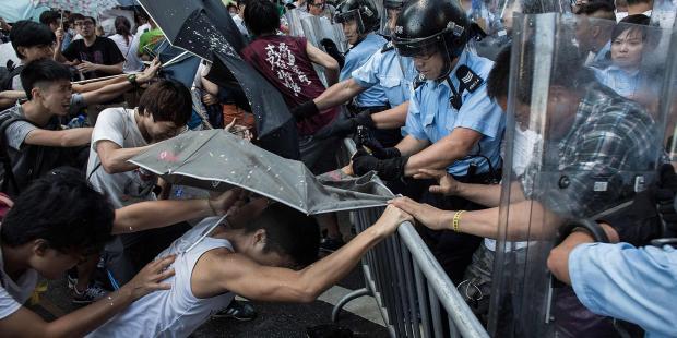 民主化を求める抗議行動で警察と衝突し、催涙スプレーから傘で身を守る学生たち。(C)Lam Yik Fei/Getty Images