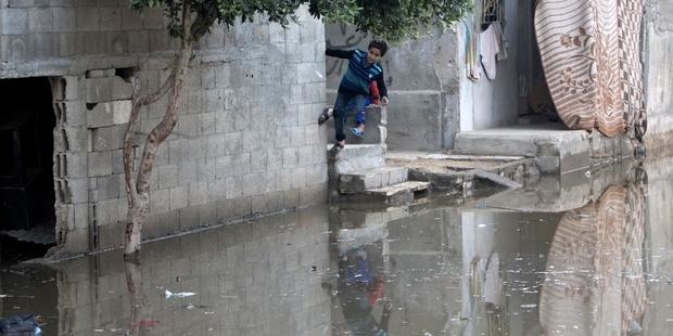 停電のため処理できない下水で溢れかえる通りで遊ぶ子どもたち(ガザ地区南部)(C)MAHMUD HAMS/AFP/Getty Images