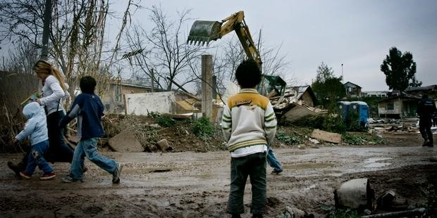 A boy watches an excavator destroy homes during the Casilino 900 forced eviction, Italy, 2009.  © Christian Minelli