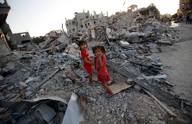 イスラエル軍に破壊された家の瓦礫の上を歩く姉妹 2014年8月12日 (C)Mahammed-Saber-epa
