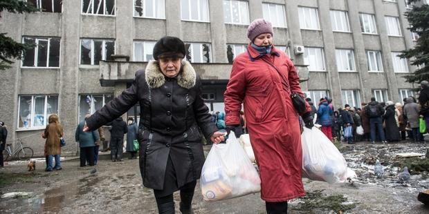 戦闘の最前線、東ウクライナのデバリツェボで人道支援物資を運ぶ人びと © VOLODYMYR SHUVAYEV/AFP/Getty Images