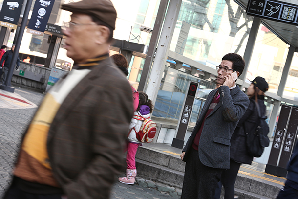 Choi Hyun-joon, a North Korean living in Seoul, Korea, using a phone outside a downtown subway station. He was unable to get in touch with his daughter, Choi Ji-woo, when he fled North Korea, due to the country's restrictions on international phone calls.