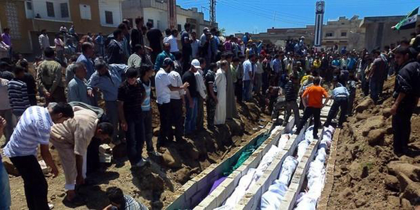 Houla residents bury the bodies of dozens of people killed in the Syrian military's assault on the town.